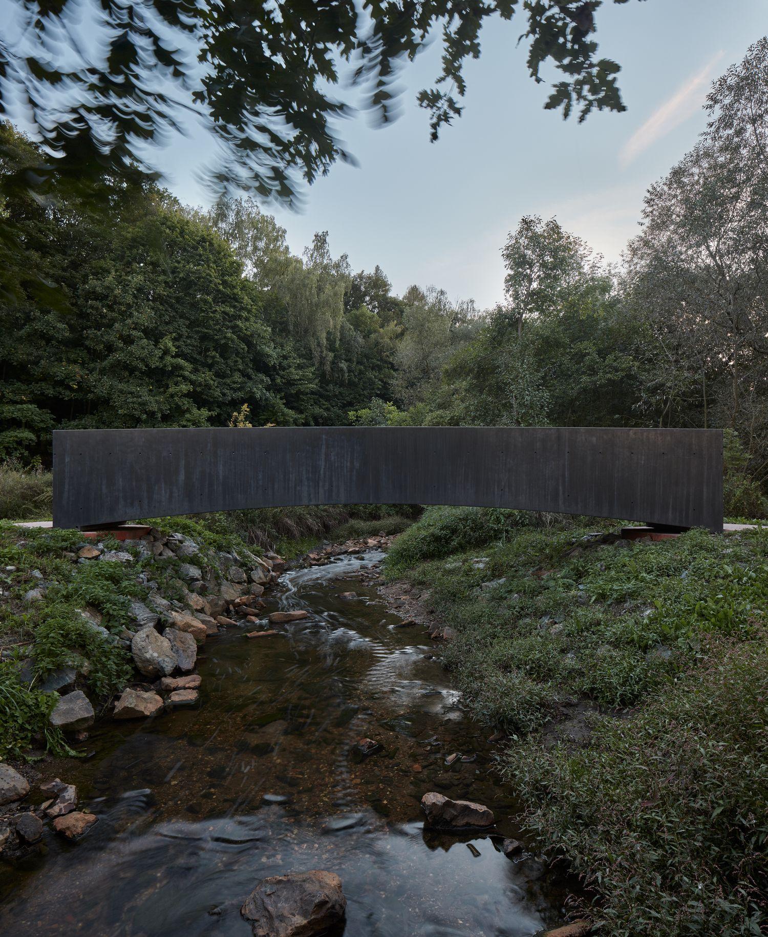 """Sijos formos tiltas grakščiai peršoka upelį ir mezga architektūros dialogą su gamta (arch. """"Aoc"""")"""